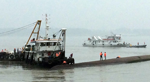 "Chinese rescue boats are seen alongside a capsized passenger ship carrying more than 450 people which sunk in the Yangtze river, triggering a rescue effort hampered by strong winds and heavy rain off Jianli in China's Hubei province on June 2, 2015.  The ship named Dongfangzhixing, or ""Eastern Star"", was headed from the eastern city of Nanjing to the southwestern city of Chongqing when it sank in the Jianli section of the river.           CHINA OUT      AFP PHOTO"