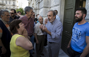 People, most of them pensioners, argue with a staff member (C) outside a closed National Bank branch at the bank's headquarters in Athens, Greece June 29, 2015. Greece closed its banks and imposed capital controls on Sunday to check the growing strains on its crippled financial system, bringing the prospect of being forced out of the euro into plain sight. REUTERS/Marko Djurica